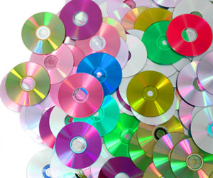 CDs and DVDs in different colors strewn on a desk
